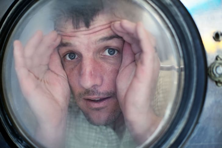 A man appears to be stuck inside a washing machine