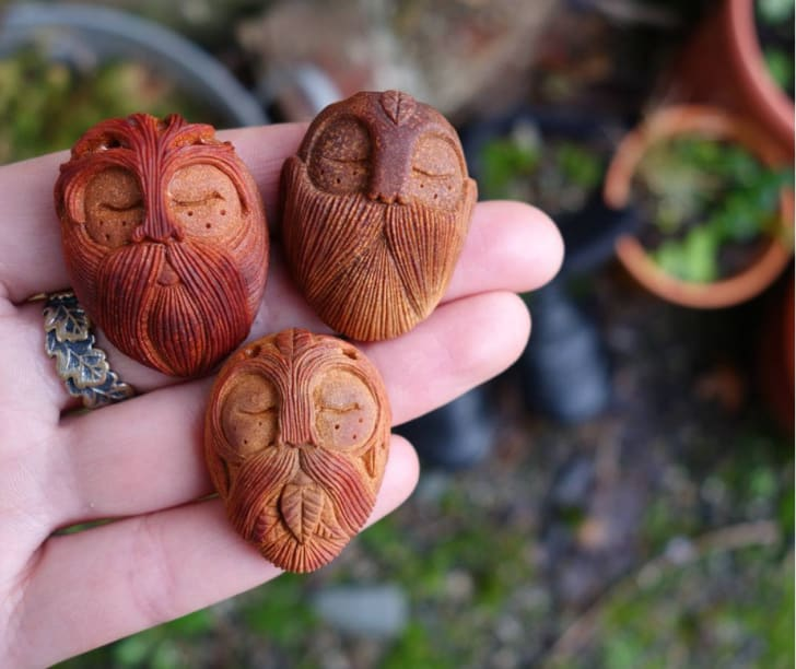 Hand holding carved faces.