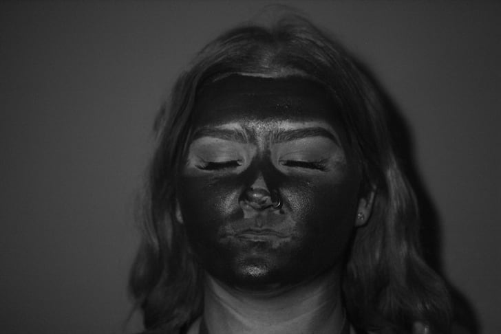 A black-and-white UV photo of a woman's blotchy sunscreen application