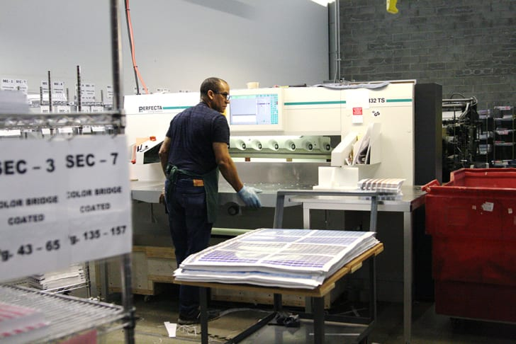 A Pantone employee stands in front of an industrial machine