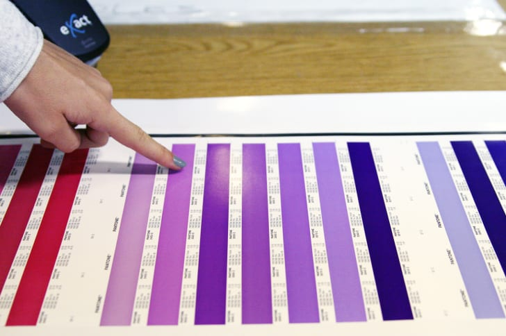 A woman's finger points to stripes of color on a Pantone press sheet.