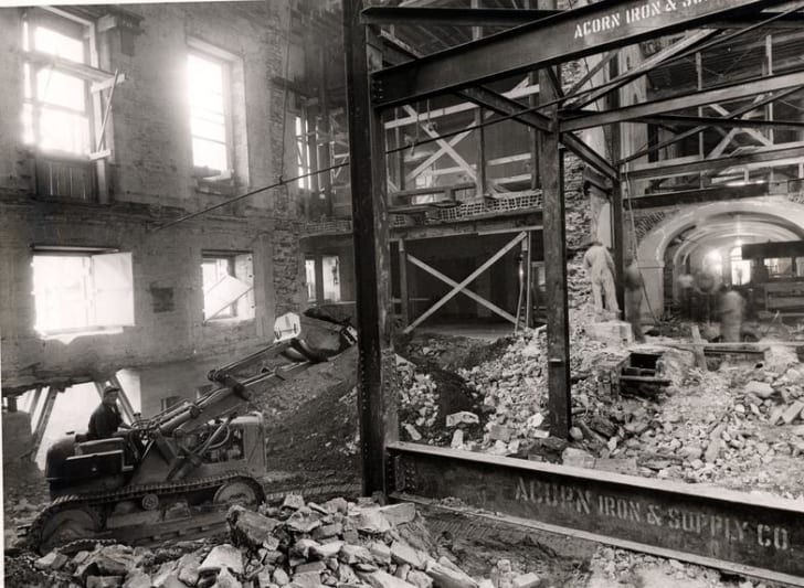 A black and white picture of a pile of debris inside of the White House, with a bulldozer, workmen and metal beams among it.
