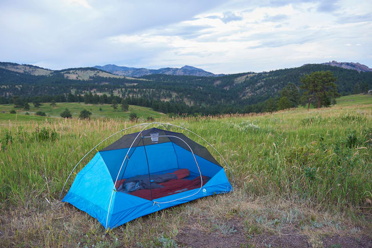 A light blue tent is set up in a field with mountains in the background.