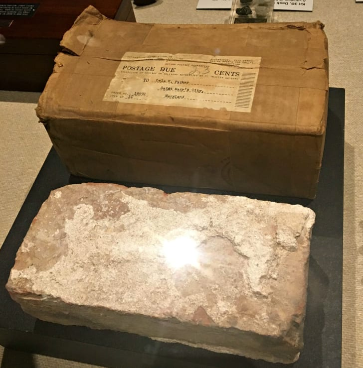 A weathered brick and the cardboard box the brick was shipped in, both under a display case.