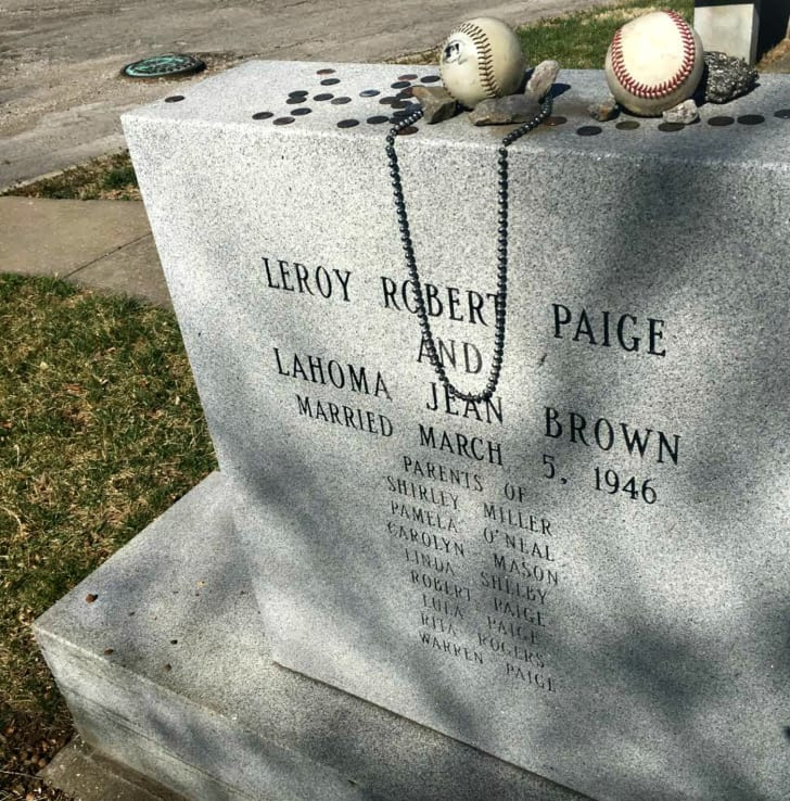 The granite gravestone of baseball legend Satchel Paige, with an engraving about his marriage and children. Fans have left baseballs, coins, and a necklace along the top of the stone.