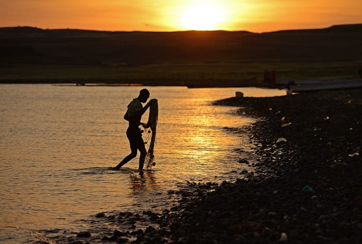 fisherman from the El Molo tribe walks back with his net at sunrise in the village of Komote