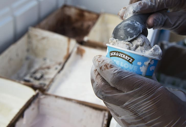 employee of Ben & Jerry's scoops ice cream into a cone