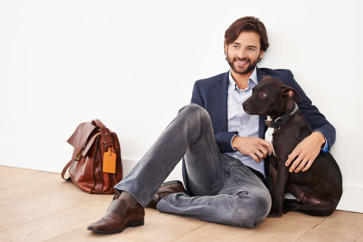 Man in work attire sits on floor with a dog.