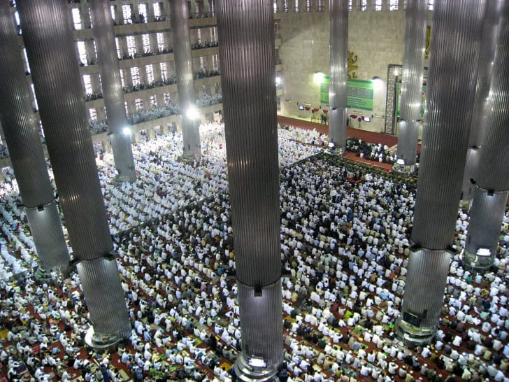 An aerial shot looking down at thousands of Muslims kneeling in prayer at a mosque in Jakarta.