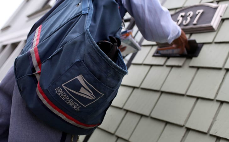 postal worker places letters in a mailbox
