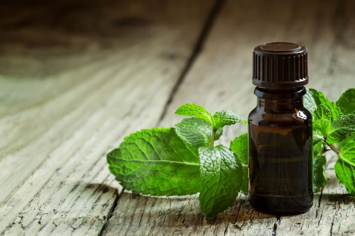 A small brown vial surrounded by sprigs of mint leaves and sitting on a wooden countertop.