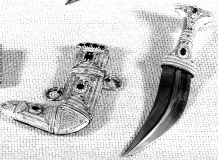 A black and white picture of a dagger and scabbard on a woven background. The scabbard is ornate and bejeweled, as is the hilt of the dagger.