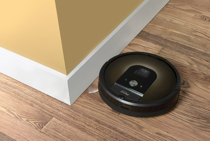 A robot vacuum skirts the wall of a room with wooden floors.