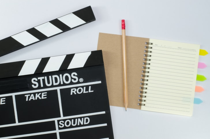 Slate film and notebook on a white background.