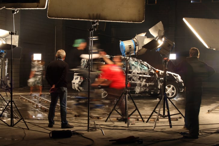 Members of a film crew standing near a car covered in water or soap under lights.