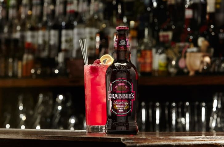 A bottle of raspberries Crabbie's and a glass sit on a bar