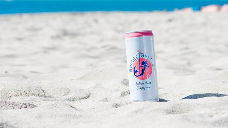 A can of Spiked Seltzer with a mermaid logo on the beach