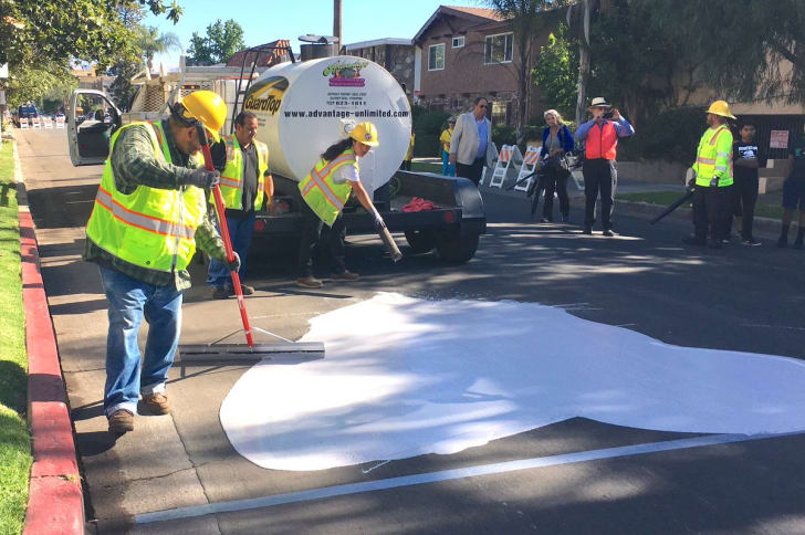 City workers spread CoolSeal coating on a street while residents look on