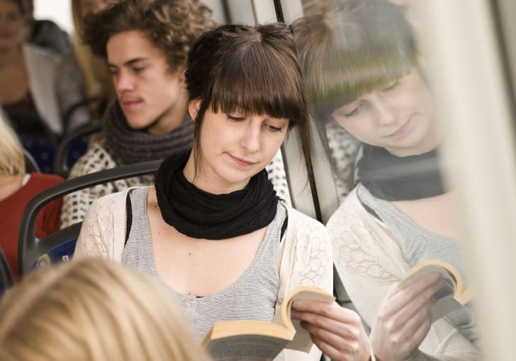 Woman reading a book on the bus
