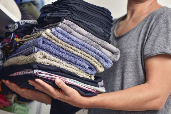 Young man holding a folded pile of clean laundry