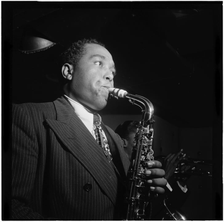 """Black and white photo of jazz musician Charlie """"Bird"""" Parker playing the saxophone."""