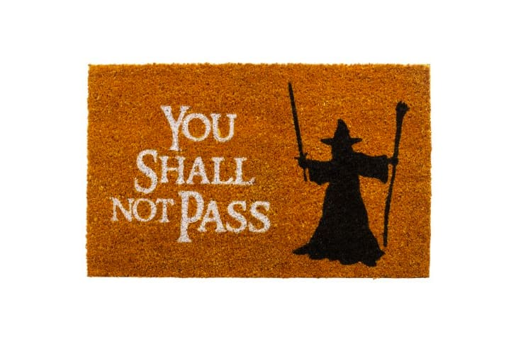 "A doormat reads ""You shall not pass"" with a silhouette of Gandalf on it"