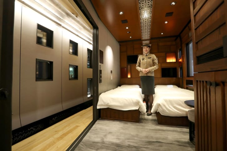 A female crew member in a brown uniform stands between two twin beds made up with white sheets in the Shiki-Shima luxury suite