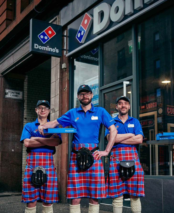 Scottish Domino's employees wearing red and blue kilts