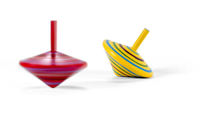 Two wooden and colorful spinning tops