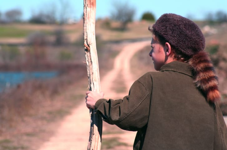 Young boy wearing a coon skin cap and carring a walking stick