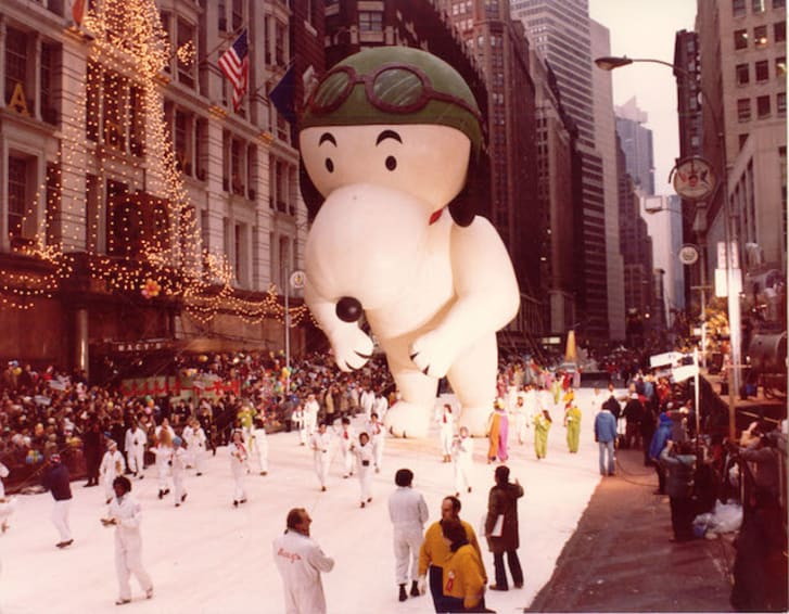 A vintage photo of a Snoopy balloon at a Macy's Thanksgiving parade
