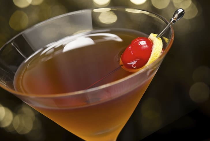 Manhattan cocktail garnished with a cherry and lemon