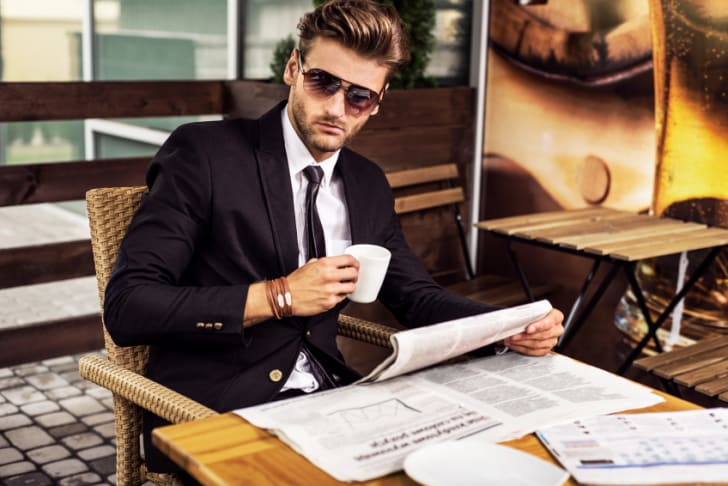 A stylish man reading a newspaper at an outdoor cafe