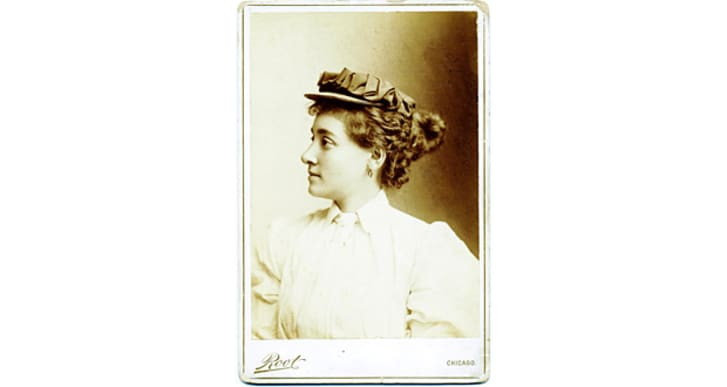 A side profile portrait of Annie Londonderry in a hat and puffed-sleeve blouse
