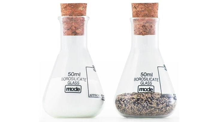 Two salt and pepper shakers shaped like glass beakers with cork stoppers