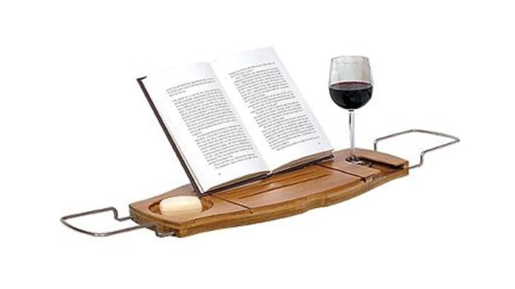An open book, a wine glass, and a bar of soap on a bathtub caddy