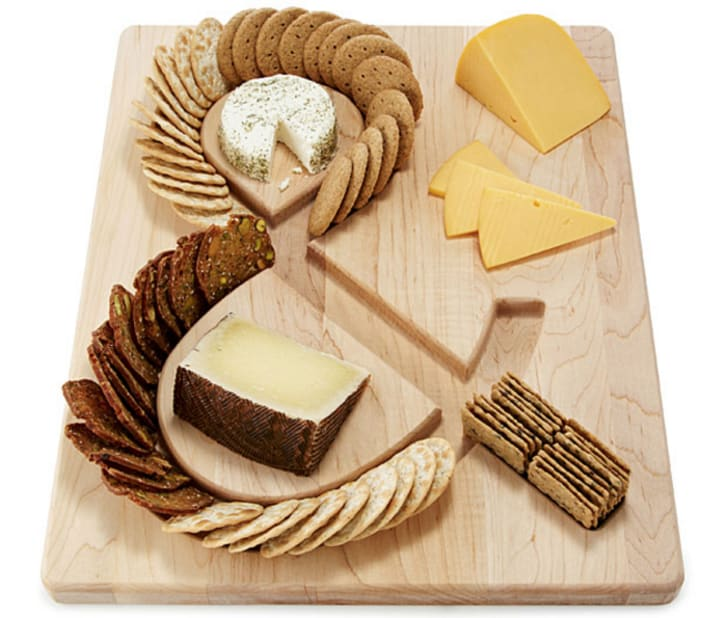 A cutting board with an ampersand engraved into it, with crackers resting in the groove