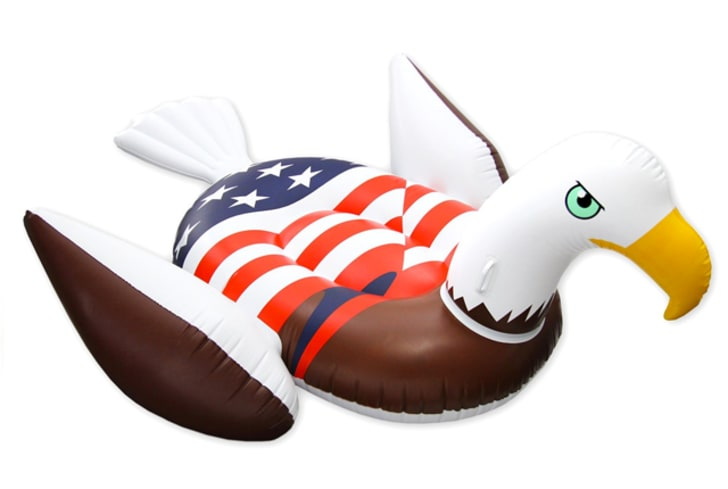 A pool float shaped like an eagle with the American flag on its back