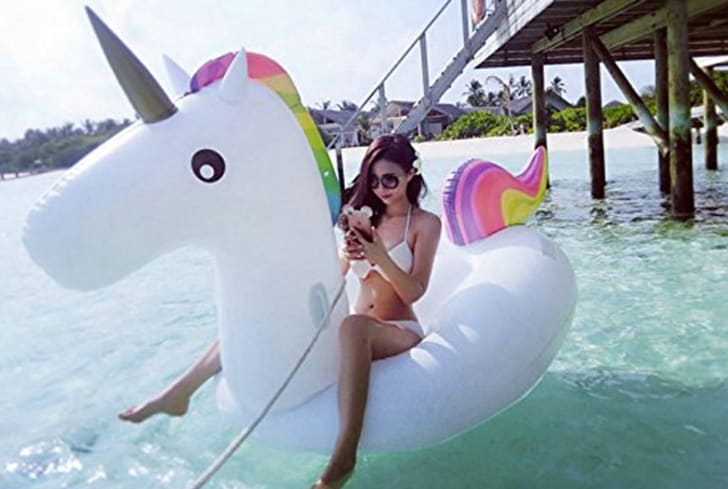 A woman sits on a giant inflatable unicorn pool float at the beach.