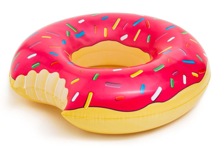 A pool float shaped like a pink doughnut with a bite taken out of it