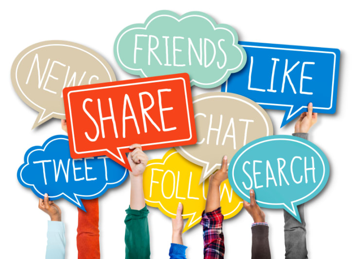 Group of hands holding up speech bubbles with social media concepts