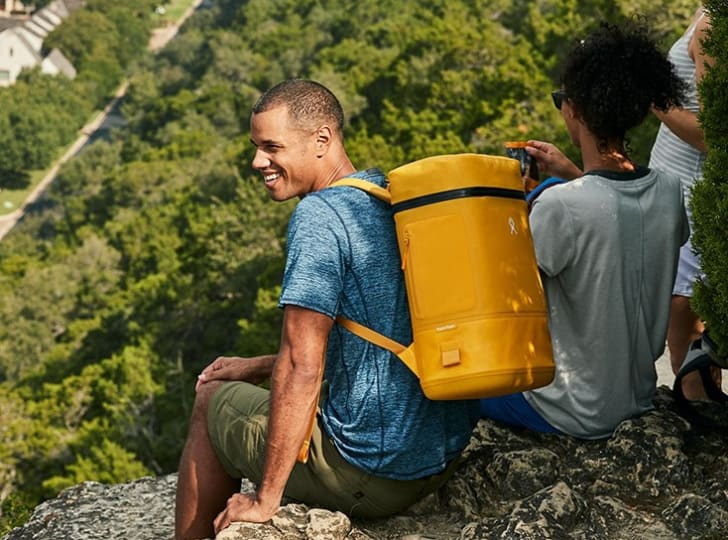 A man perches on an outlook wearing a yellow cooler backpack