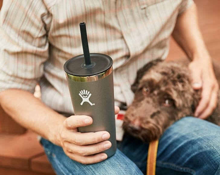 A man holds a Hydro Flask straw tumbler while a dog places its head on his lap.