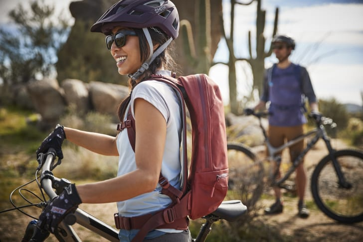 A mountain biking woman wears a Hydro Flask hydration pack