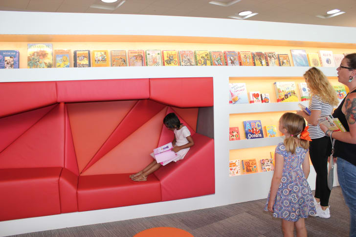 Child reading in reading nook in library.