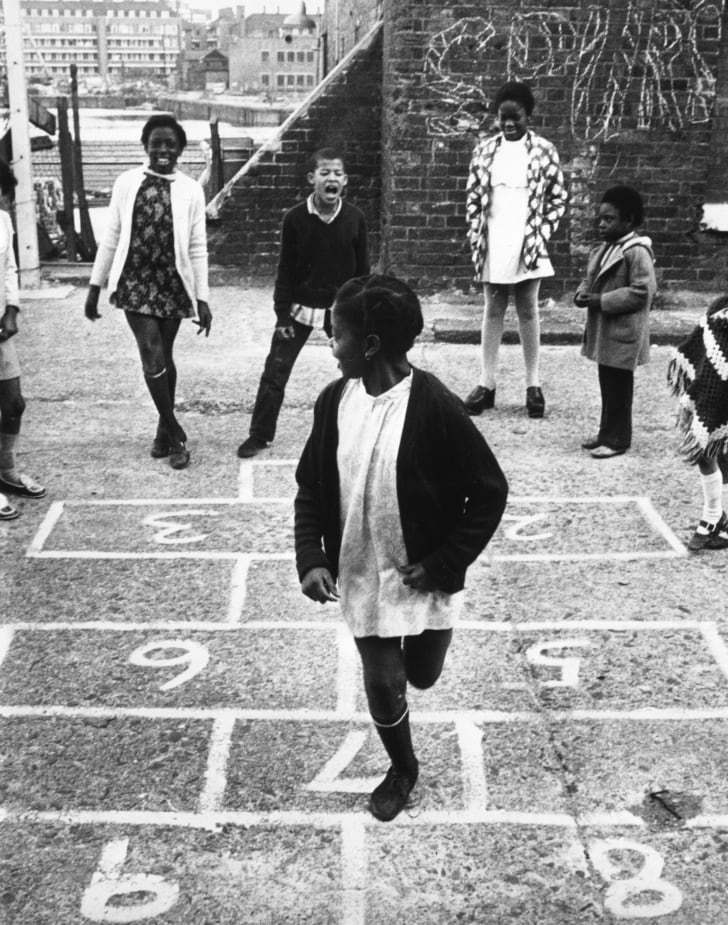 Young girls play hopscotch on a sidewalk in the 1970s