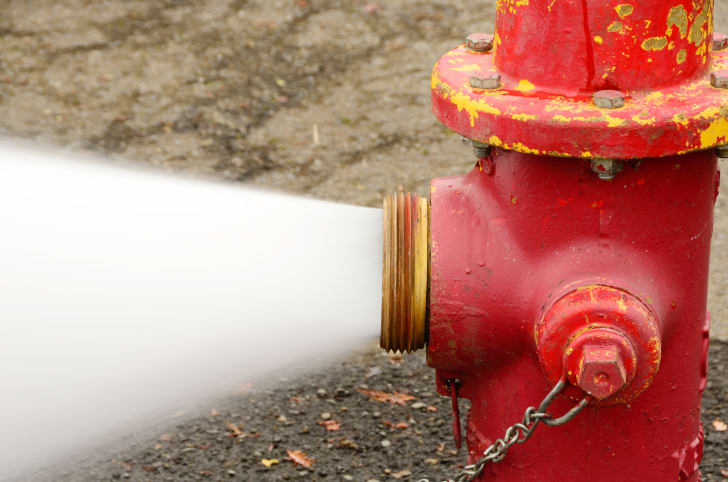Red fire hydrant gushing water