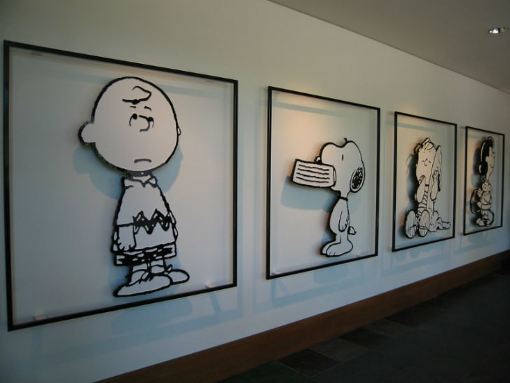Wall art featuring 'Peanuts' characters Charlie Brown, Snoopy, and Linus are pictured