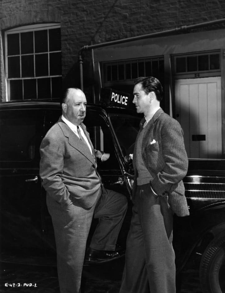 Director Alfred Hitchcock speaks with actor Richard Todd during the filming of 'Stage Fright'