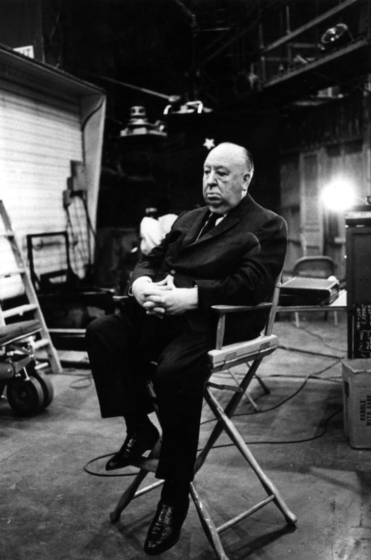 Director Alfred Hitchcock sits in his chair on the set of the film 'Topaz'